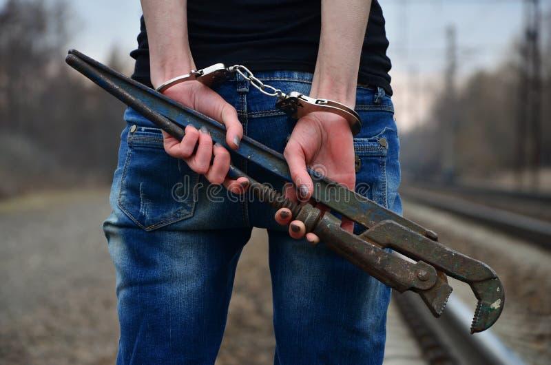 Het meisje in handcuffs met de pijpmoersleutel op het spoorwegspoor royalty-vrije stock afbeeldingen
