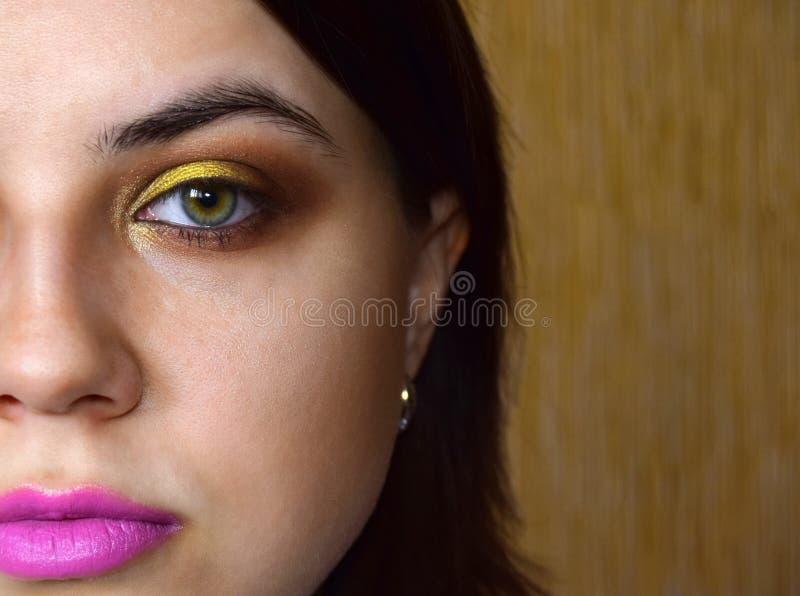 Het meisje heeft een make-up van een groen oog in gele en gouden tonen Op lippen is er een roze lippenstift royalty-vrije stock afbeelding