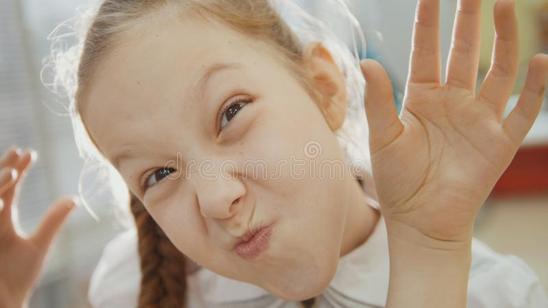 Het meisje heeft grappig en toont in de neus en de tong van het camerabiggetje stock foto