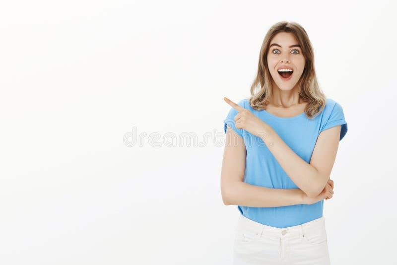 Het meisje heeft om het even wat niet beter gezien Portret van geïmponeerde gelukkige jonge vrouw met blonhaar, het glimlachen en stock foto