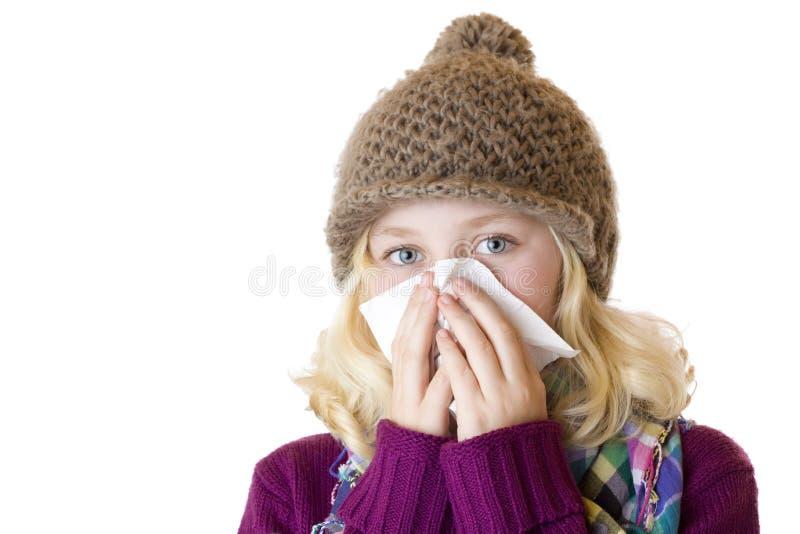 Het meisje heeft snuifje en blaast haar neus met een weefsel royalty-vrije stock afbeeldingen
