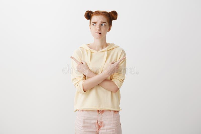 Het meisje heeft twijfels over haar keus Knappe roodharigevrouw met twee broodjeskapsel die wapens over borst kruisen en royalty-vrije stock fotografie