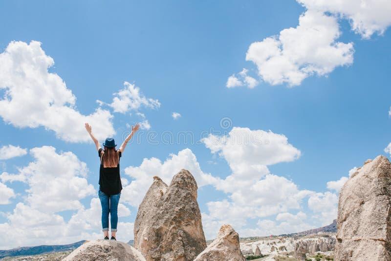 Het meisje heft omhoog haar handen in een teken van overwinning en succes op Jong mooi reismeisje bovenop een heuvel binnen stock afbeelding