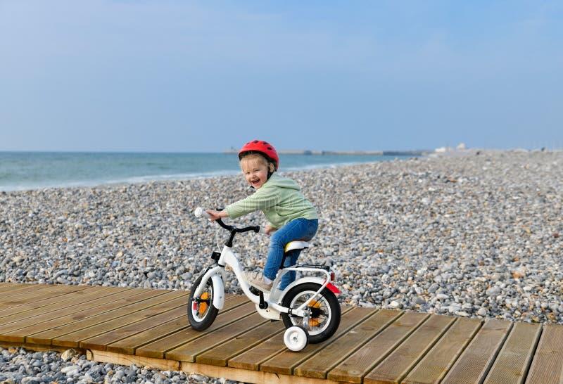 Het meisje in helm leert het berijden van een vierwielige fiets royalty-vrije stock fotografie