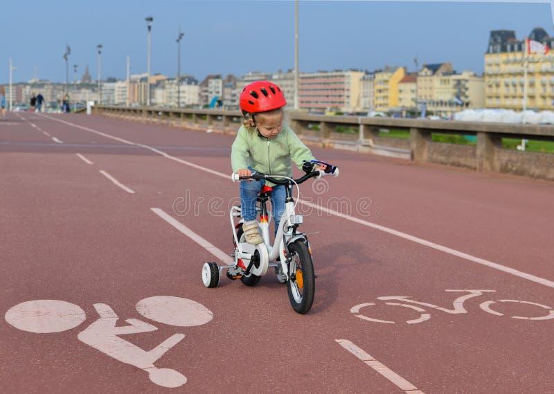 Het meisje in helm leert het berijden van een vierwielige fiets stock afbeelding