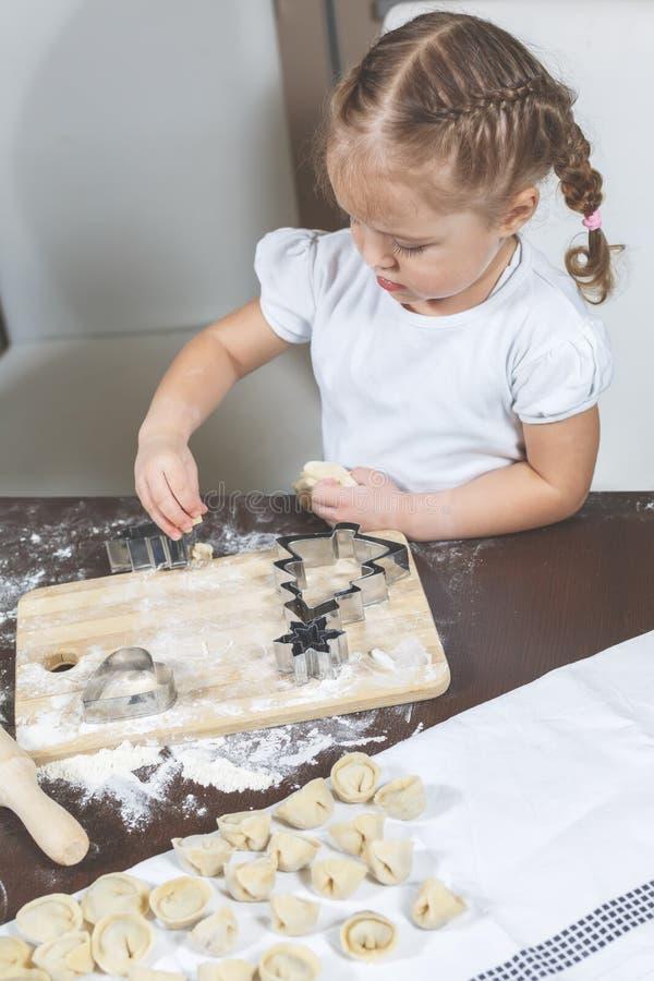 Het meisje helpt om bollen thuis te maken royalty-vrije stock afbeeldingen