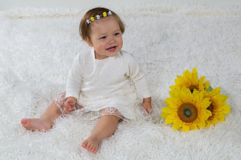Het meisje is het lachen zitting op zacht wit tapijt stock foto's