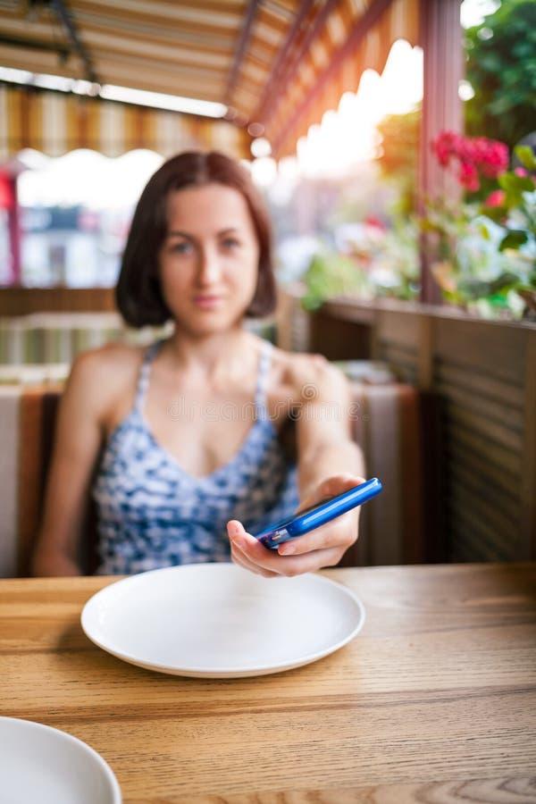 Het meisje in het restaurant houdt de telefoon stand royalty-vrije stock fotografie