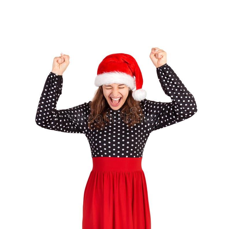Het meisje hief omhoog haar handen van geluk en overwinning op emotioneel meisje in Kerstmishoed van de Kerstman dat op witte ach stock afbeelding