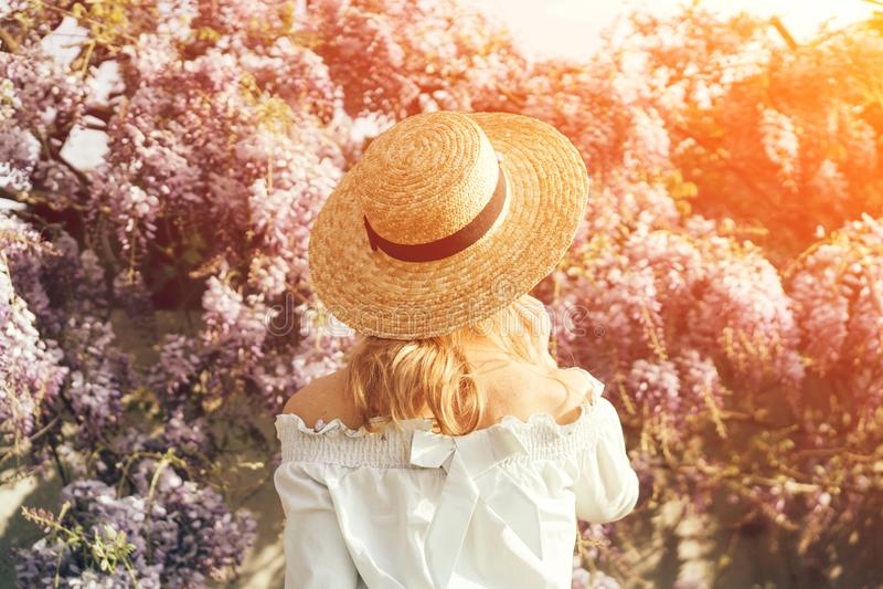 Het meisje in hoed bekijkt zonsondergang stock afbeelding