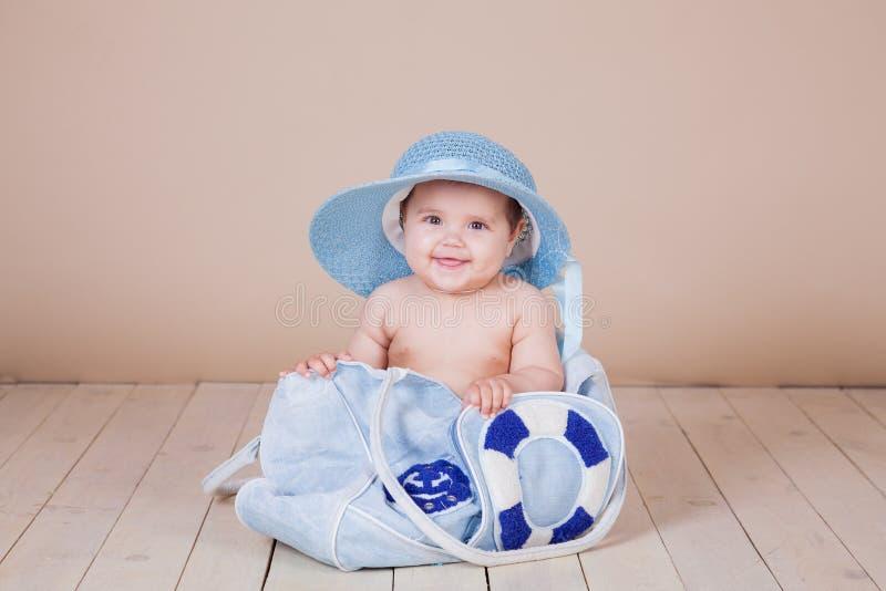 Het meisje in hoed zit in strandzak stock afbeeldingen