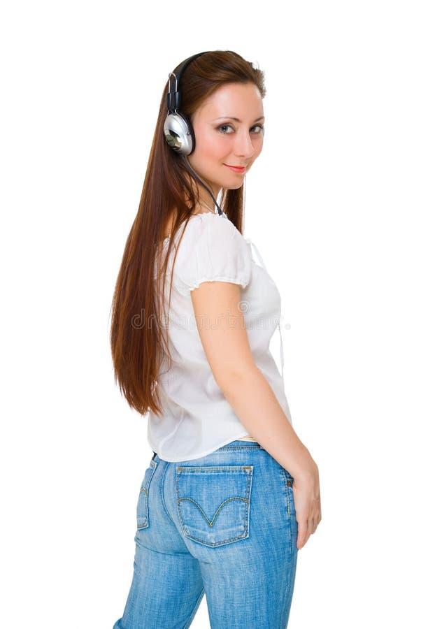 Het meisje in hoofdtelefoons luistert aan muziek royalty-vrije stock foto