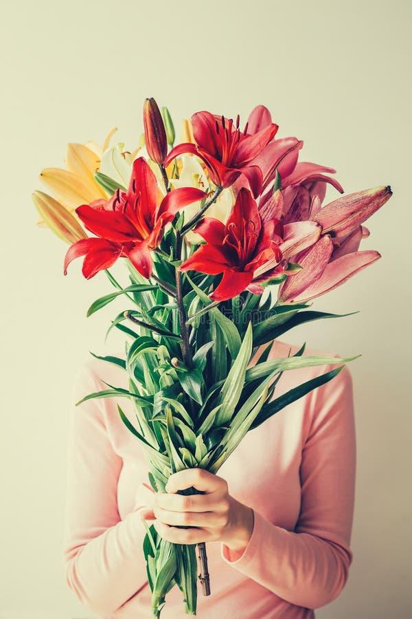 Het meisje houdt boeket van lelies in haar handen, verbergt gezicht in bloemen stock afbeelding