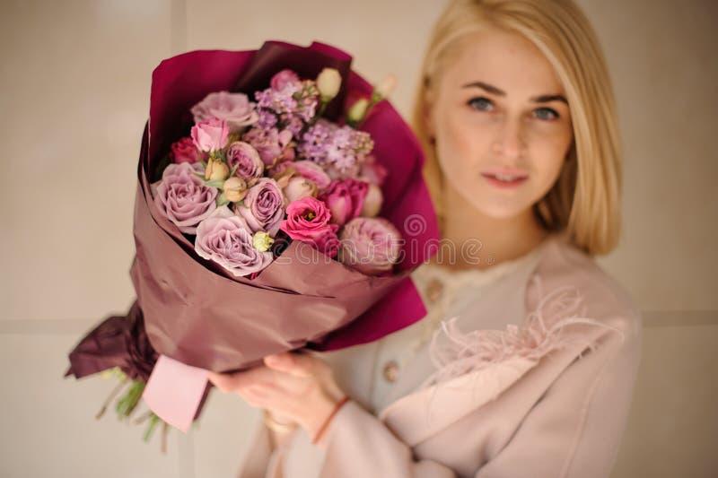 Het meisje houdt boeket van rozen in pakpapier stock afbeeldingen