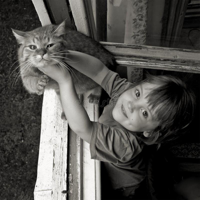 Het meisje houdt de kat door te stellen aan de fotograaf Zwart-witte fotografie royalty-vrije stock afbeeldingen