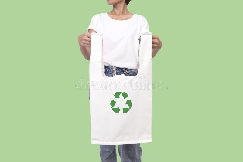 Het meisje houdt de stof van het zakcanvas met kringloop geïsoleerd symbool stock afbeelding