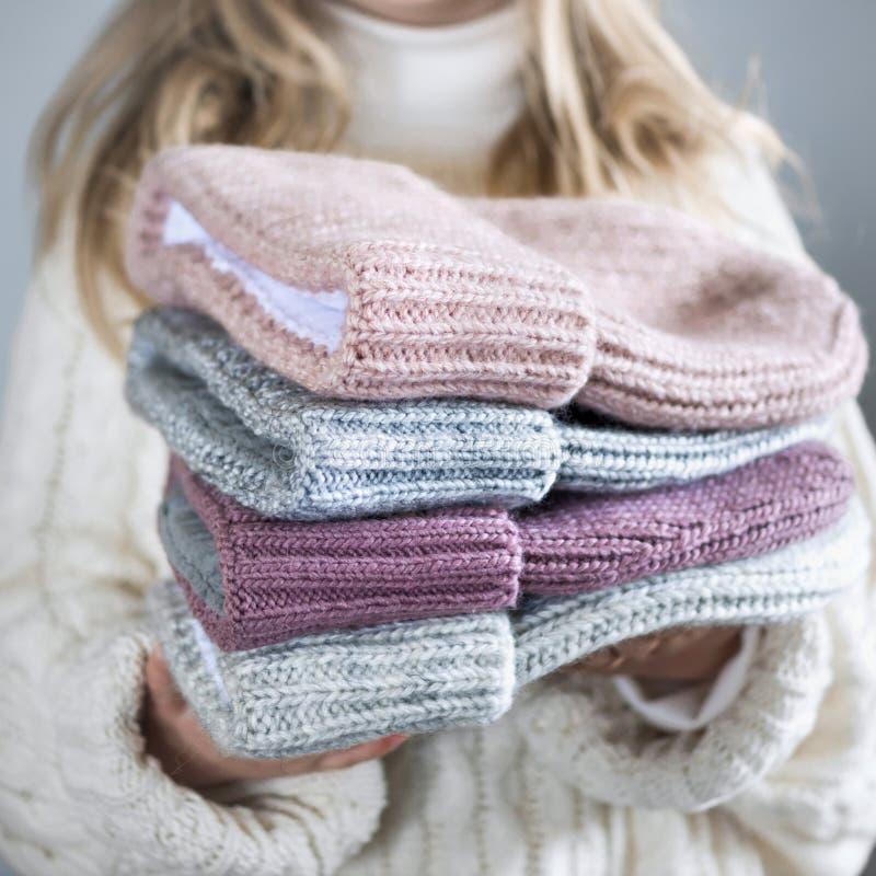 Het meisje houdt de winter gebreide hoedenclose-up op grijs royalty-vrije stock fotografie