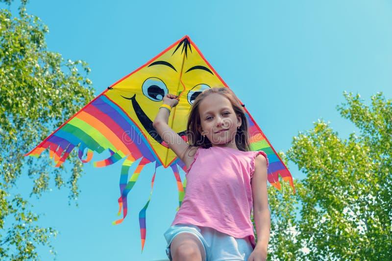 Het meisje houdt een heldere vlieger in haar handen en glimlacht tegen de blauwe hemel Concept de zomer, vrijheid en gelukkige ki royalty-vrije stock afbeelding