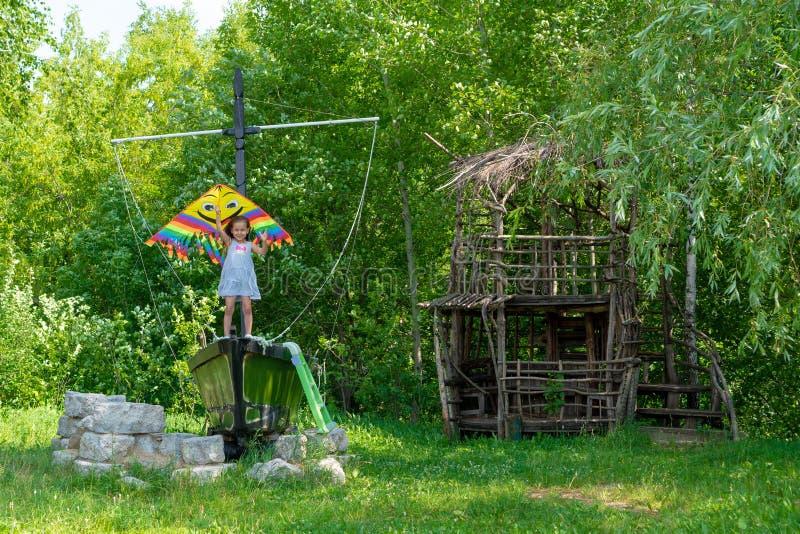Het meisje houdt een heldere vlieger in haar handen en glimlacht tegen het groene bos kleine kind van A 5 jaar oude tribunes stock foto's
