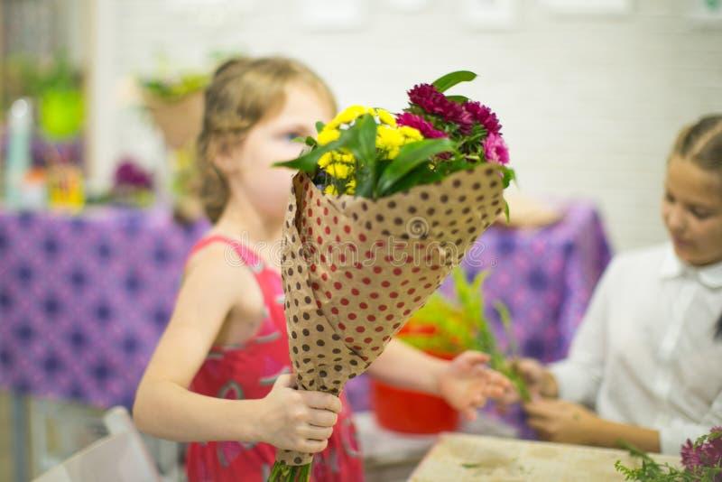 Het meisje houdt een klaar boeket van bloemen stock afbeelding