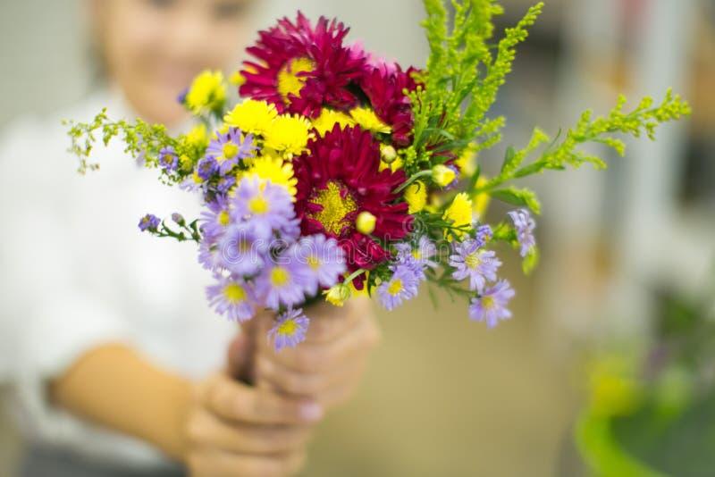 Het meisje houdt een klaar boeket van bloemen stock fotografie