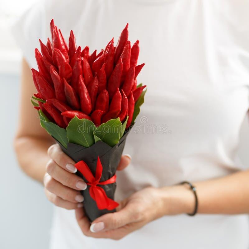 Het meisje houdt een klein boeket bestaand uit roodgloeiende peper in de vorm van een hart als gift royalty-vrije stock afbeeldingen