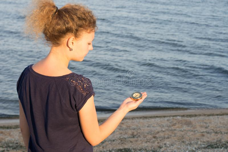 Het meisje houdt een klein kompas die op de richting op de achtergrond van het overzees wijzen royalty-vrije stock afbeeldingen