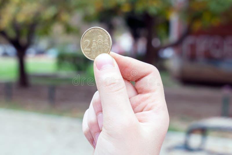 Het meisje houdt een muntstuk in haar hand Servische dinar royalty-vrije stock afbeelding