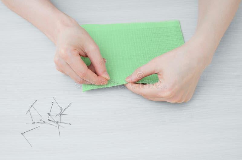 Het meisje houdt een stuk van groene doek en een naald om de stof te stikken stock foto's