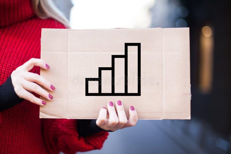 Het meisje houdt een teken met het beeld van een bedrijfsconcept voor het proces van de succesgroei stock foto