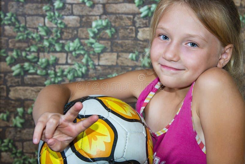 Het meisje houdt een voetbalbal stock afbeeldingen