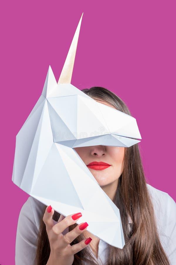 Het meisje houdt een wit 3d papercraftmodel van Eenhoorn Minimaal Art Concept stock afbeelding