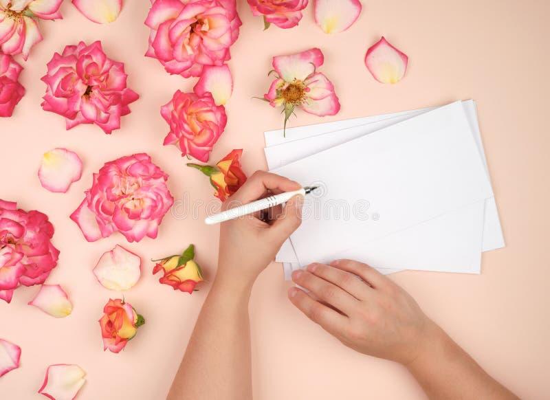 het meisje houdt in haar linkerhand een witte pen en ondertekent enveloppen op een perzikachtergrond royalty-vrije stock foto's