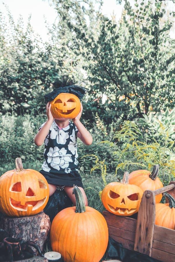 Het meisje houdt Halloween-pompoen voor haar gezicht Het kind kleedde zich in zwarte tussen hefboom-o-lantaarn decoratie, truc of stock afbeelding