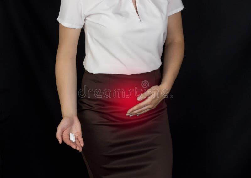 Het meisje houdt op de lagere buik, geuren en houdt in haar handzetpil, seksuele besmetting stock afbeeldingen