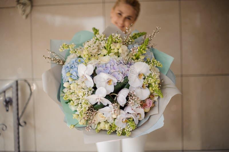 Het meisje houdt reuzeboeket van verschillende bloemen royalty-vrije stock afbeelding