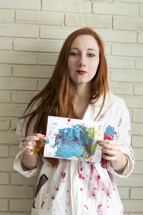 Het meisje houdt tekening met de vingers en de acrylverven wordt geschilderd die stock afbeelding