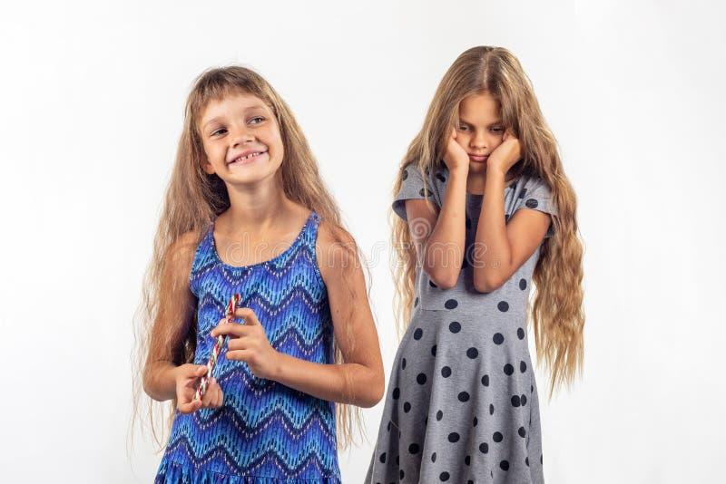 Het meisje houdt vreugdevol droevig suikergoed, ander meisje op de achtergrond stock foto