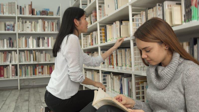 Het meisje hurkt dichtbij het boekenrek bij de bibliotheek stock afbeeldingen