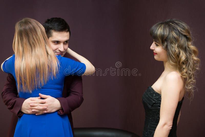 Het meisje is jaloers van een jonge man aan een andere vrouw royalty-vrije stock afbeelding