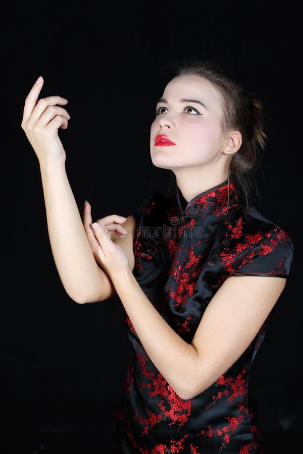 Het meisje in Japanse blouse danst omhoog en kijkt stock foto