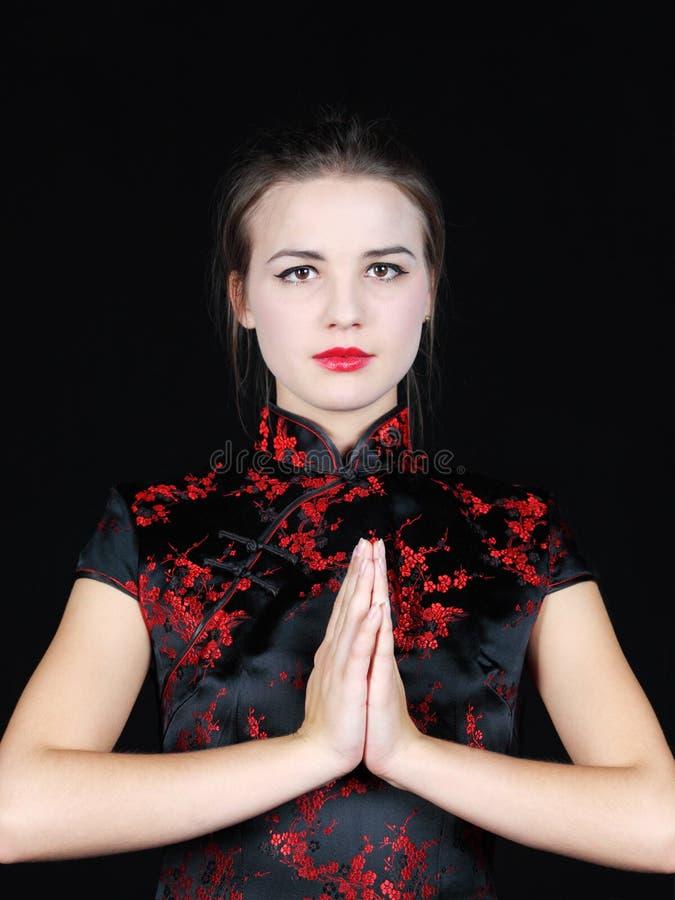 Het meisje in Japanse zijdeblouse zet handen vóór borst stock fotografie