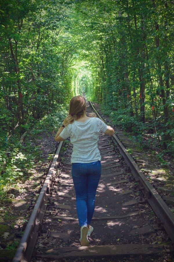 Het meisje in jeans en een witte T-shirt is op het spoor Spoorweg tussen de bomen die tot een tunnel van groene bladeren leiden stock foto