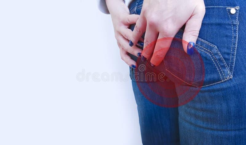 Het meisje in jeans lijdt aan de ongezonde pijn van het hemorroïdenconcept stock afbeeldingen