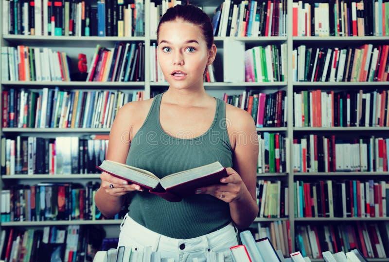 Het meisje kiest een boek in de bibliotheek stock afbeelding
