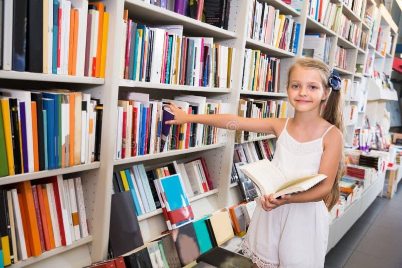 Het meisje kiest een boek in de bibliotheek royalty-vrije stock foto