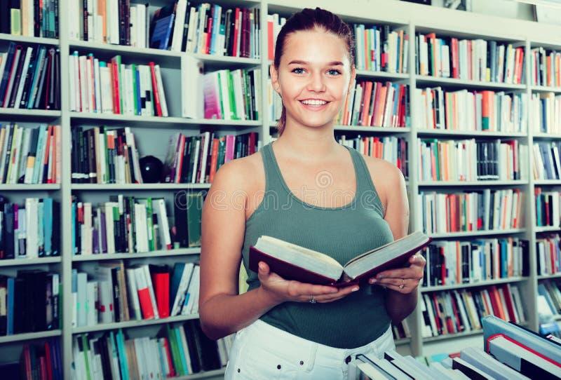Het meisje kiest een boek in universitaire bibliotheek royalty-vrije stock foto