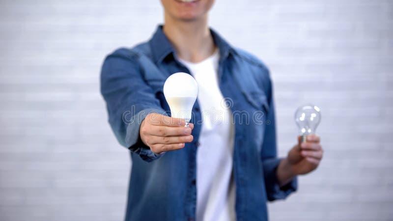 Het meisje kiest energie - besparing geleide bol in plaats van gloeilamp, efficiency royalty-vrije stock fotografie
