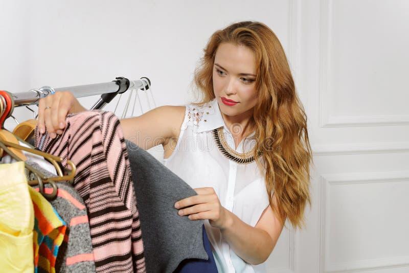 Het meisje kiest kleren in klerenwinkel royalty-vrije stock afbeelding