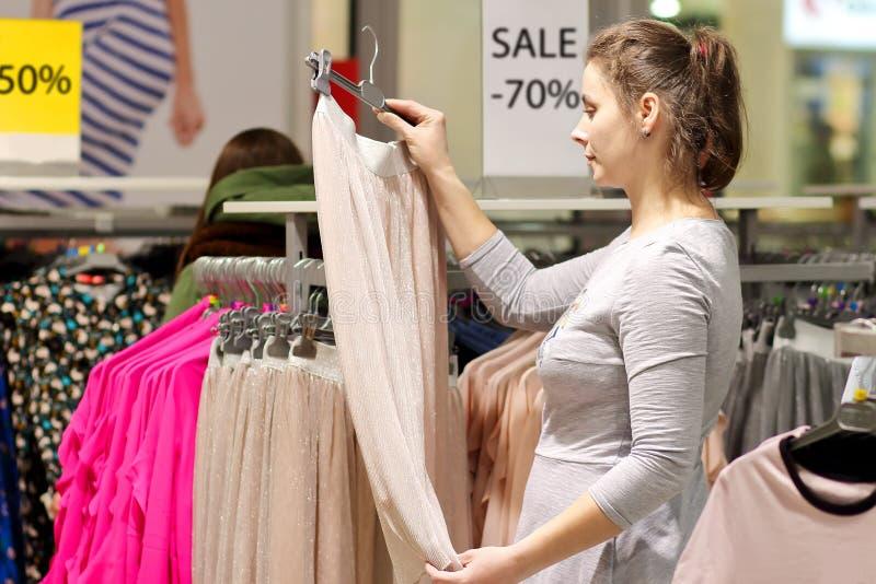 het meisje kiest kleren in modieuze boutique Het kopen van kleren op verkoop Zwart vrijdagconcept De manieropslag schikte een tot stock fotografie